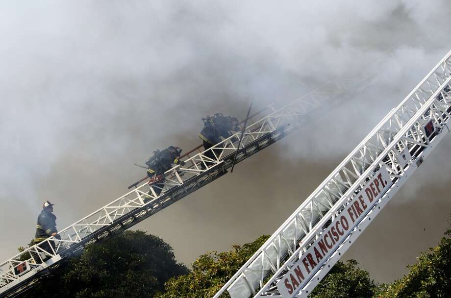 Firefighters retreat from the roof while battling a four-alarm fire at Pierce Street and Golden Gate Avenue in San Francisco, Calif. on Thursday, Dec. 22, 2011.