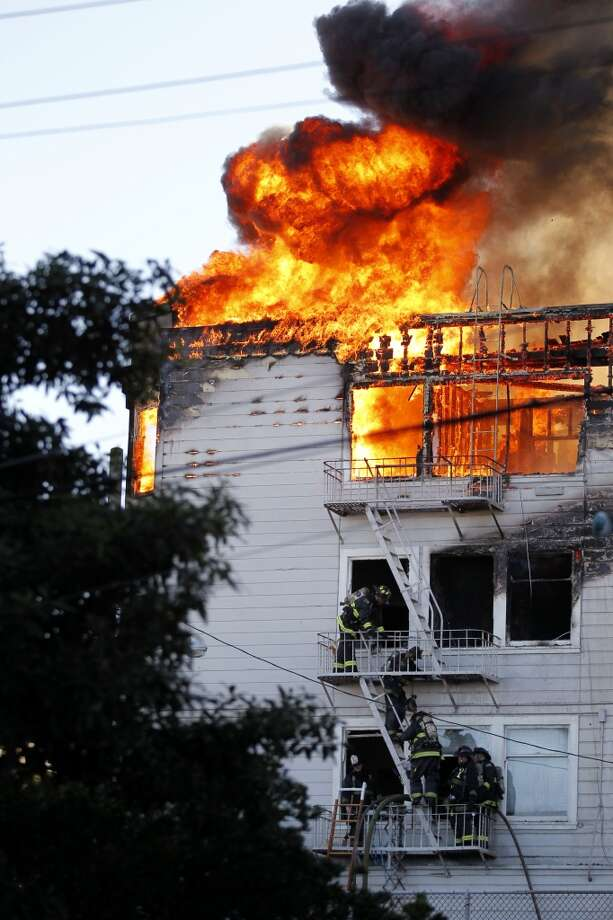 Firefighters exit a burning building on Pierce Street between Golden Gate Avenue and Turk Street on Thursday, December 22, 2011 in San Francisco, Calif.