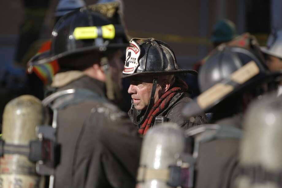 Firefighters talked after dousing a large fire in a building on the corner of Haight St. and Fillmore St. in San Francisco, Calif., on Tuesday, Sept. 27, 2011.