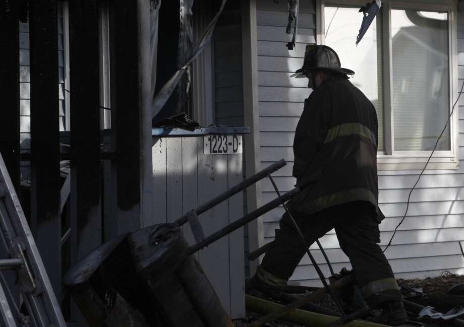 A Firefighter enters a heavily damaged apartment after an overnight fire on Treasure Island killed a 10-year-old girl in San Francisco, Calif. on Saturday, Feb. 16, 2013.