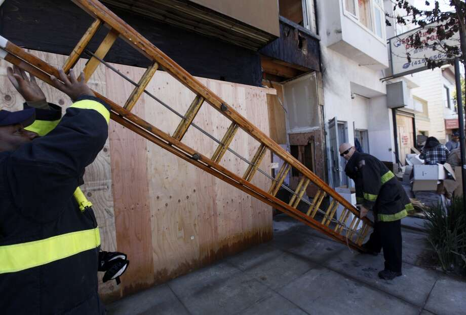 Firefighters remove a ladder next door to the San Bruno Avenue Dental Group in San Francisco, Calif. on Wednesday, June 13, 2012, which was heavily damaged by a four-alarm blaze that gutted the two-story structure and an adjacent apartment building on Tuesday.