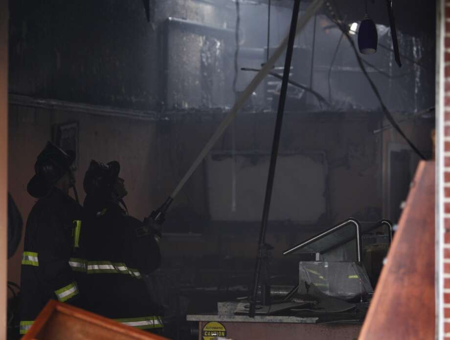 Firefighters douse hot spots inside King\'s Coffee shop after a four-alarm fire heavily damaged three businesses on the 1500 block of Ocean Avenue in San Francisco, Calif. on Tuesday, Aug. 7, 2012.