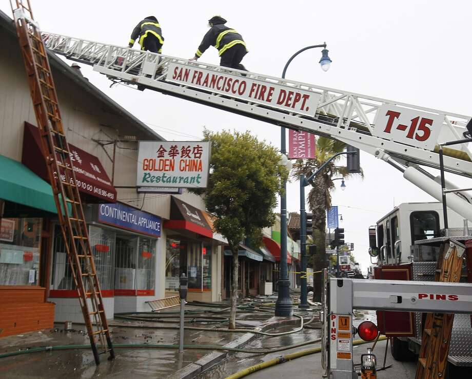 Firefighters climb a ladder to clean up after a four-alarm fire heavily damaged three businesses on the 1500 block of Ocean Avenue in San Francisco, Calif. on Tuesday, Aug. 7, 2012.