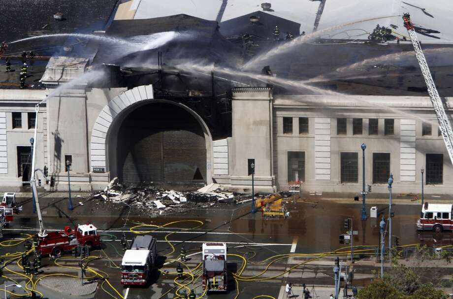 Firefighters spray down Pier 29 after a fire there in San Francisco, Calif., Wednesday, June 20, 2012.