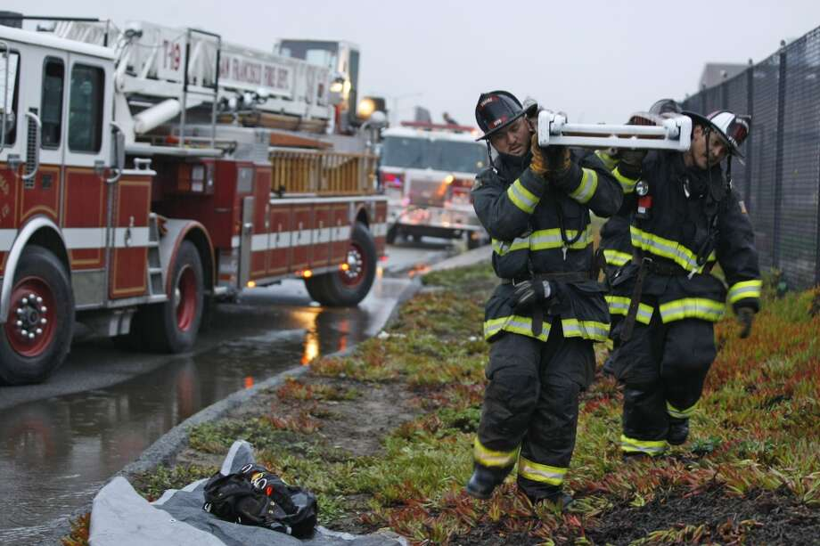 Firefighters carry a ladder to the historic Fleishhacker Pool at the San Francisco Zoo after flames inside the building began flaring up again on December 1, 2012.
