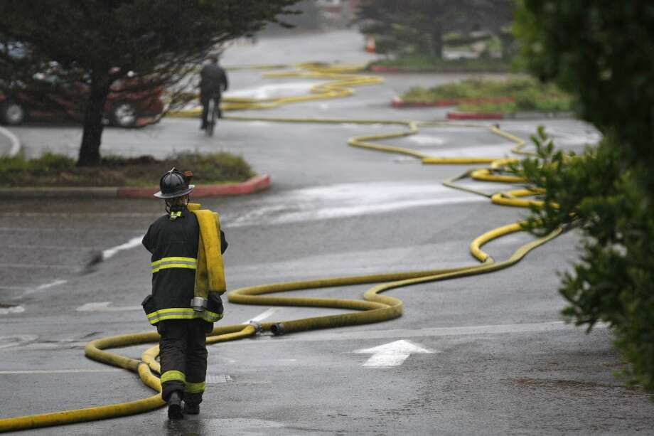 A firefighter collects hoses used to put out a fire at the historic Fleishhacker Pool in the San Francisco Zoo on December 1, 2012.