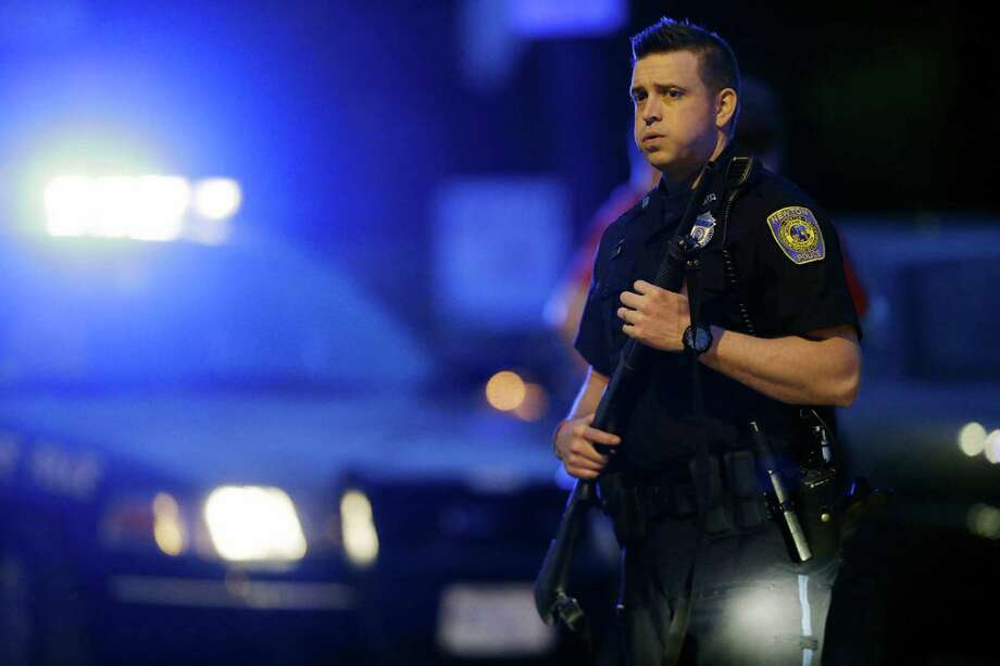 A police officer stands guard as the search for suspects in the Boston Marathon bombings continued April 19 in Watertown, Mass. An Express-News reader believes residents need to be able to protect themselves and that police are not the only ones who should have guns. Photo: Matt Rourke, Associated Press / AP