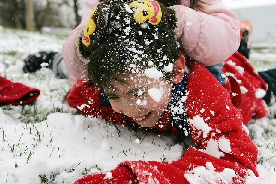 Kansas still thinks its winter: Ten-year-old Bailey Neuberger is a pretty good big brother to let his 5-year-old sister, Addison, grind his face into the snow in Hays, Kan. About 2 inches fell despite May being only a week away. Photo: Chad Pilster, Associated Press