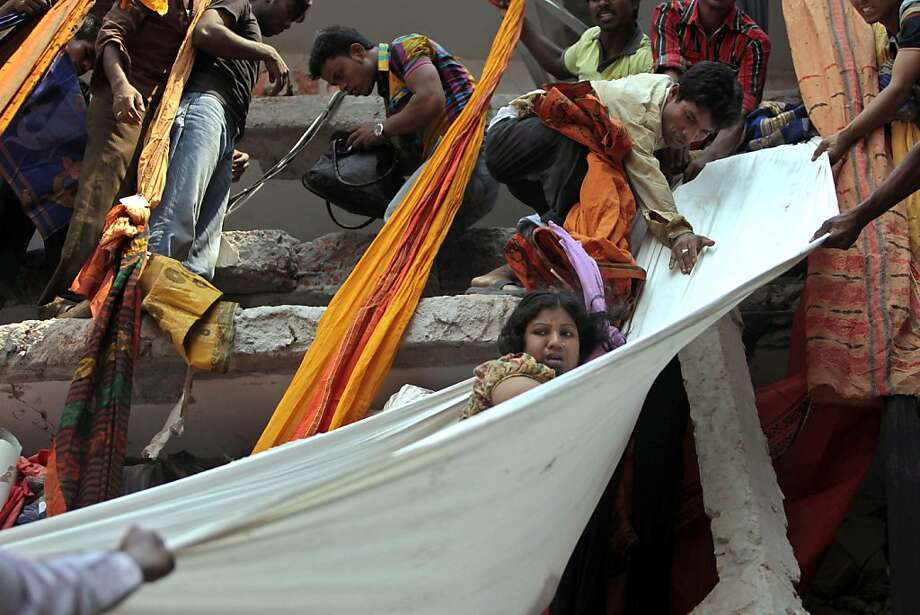 "Factory complex collapses:Rescue workers lower a survivor in a sheet after an eight-story building housing several garment factories collapsed in Savar, Bangladesh. Scores were killed and many others trapped in the rubble. An official said the building had violated construction codes and vowed the ""culprits would be punished."" Photo: A.M. Ahad, Associated Press"