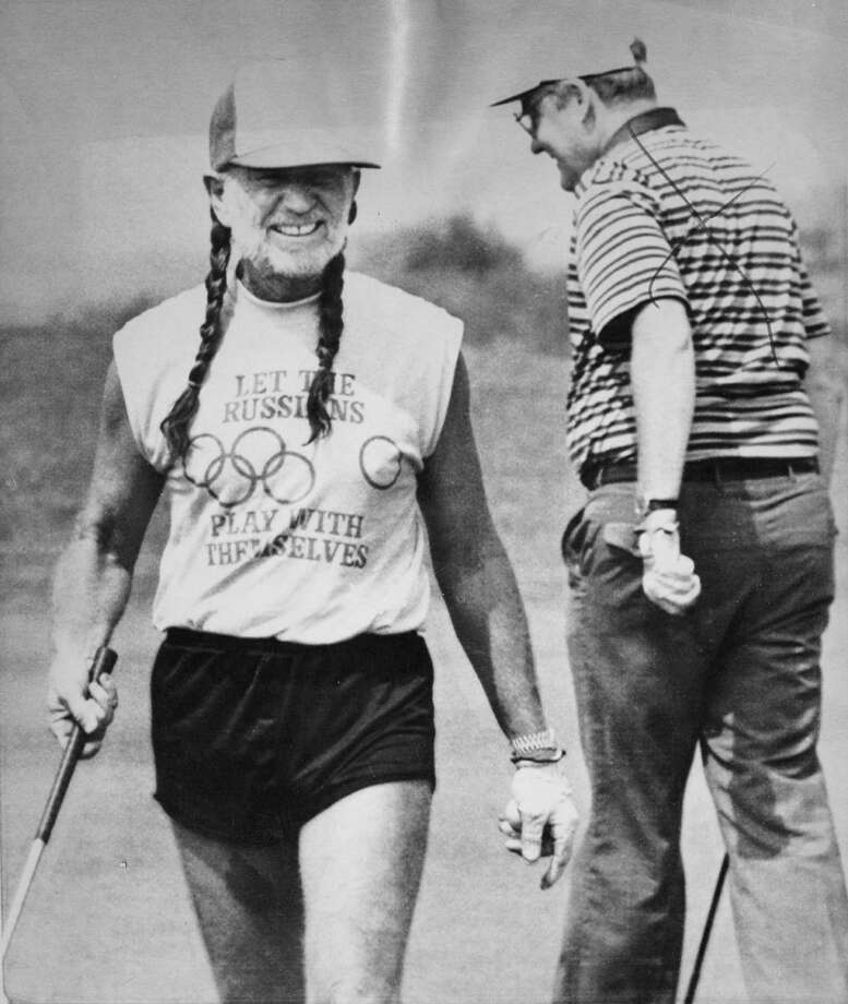 "Willie Nelson wears short shorts and a ""Let the Russians play with themselves"" t-shirt at a golf course in 1984. (AP) Photo: Willie, Houston Chronicle"