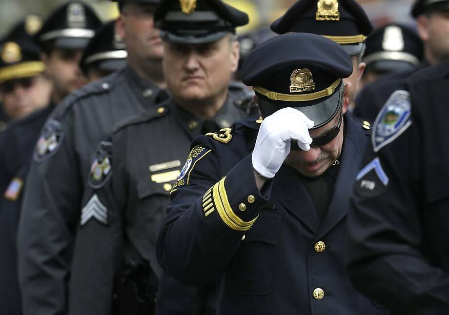 A Revere, Mass. police captain holds his cap while entering a memorial service for fallen Massachusetts Institute of Technology police officer Sean Collier, in Cambridge, Mass., Wednesday, April 24, 2013. Collier was fatally shot on the MIT campus Thursday, April 18, 2013. Authorities allege that the Boston Marathon bombing suspects were responsible.  Photo: Steven Senne, Associated Press