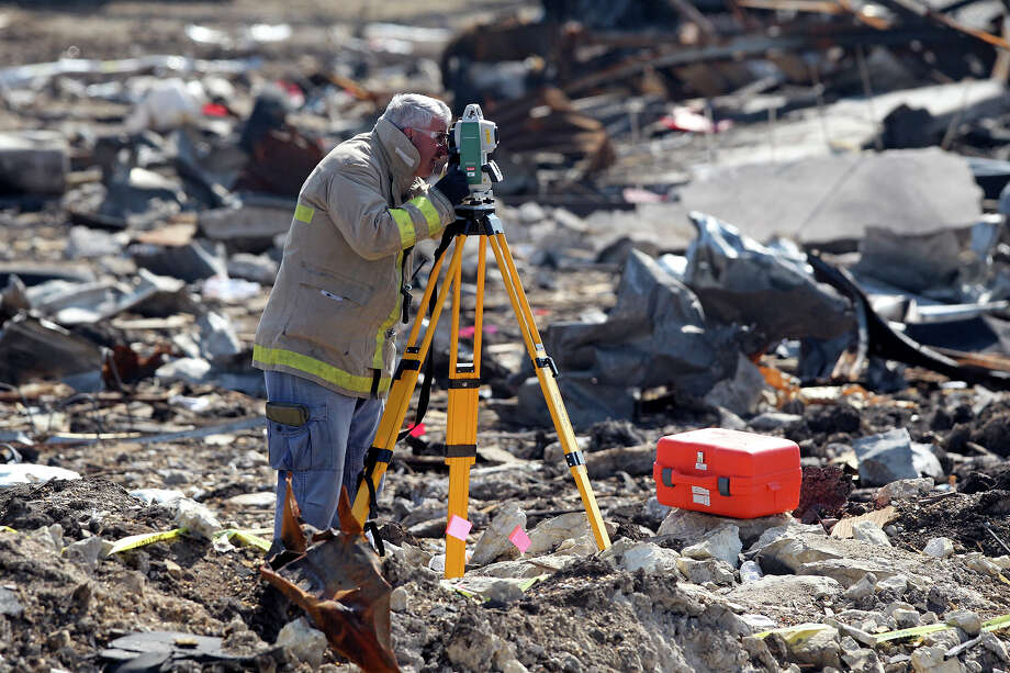 A forensic mapper works measuring the crater at the site of the fire and explosion in West, Texas on  April 24 2013. Photo: TOM REEL
