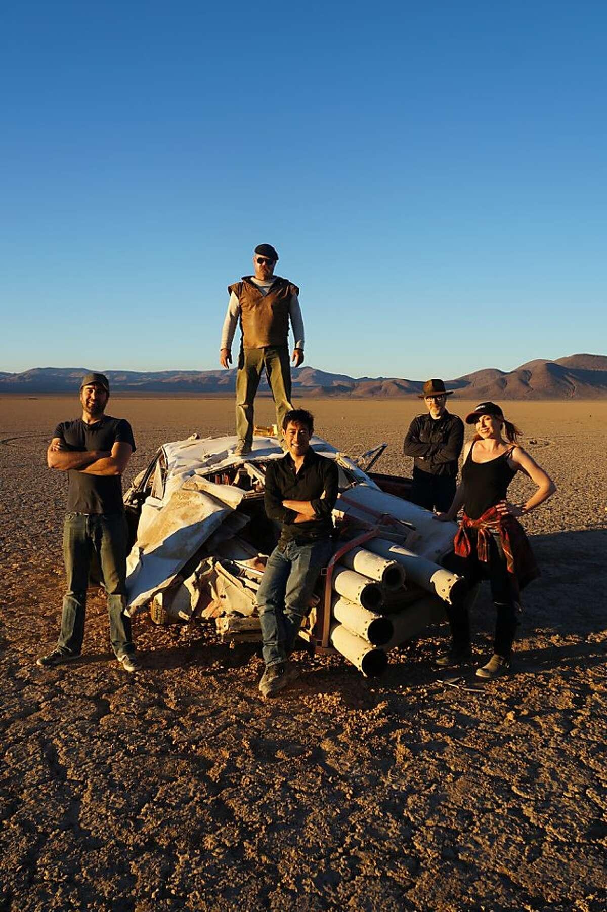 Jamie Hyneman, Adam Savage, Tory Belleci, Grant Imahara and Kari Byron pose on the crashed JATO Rocket Car after testing.