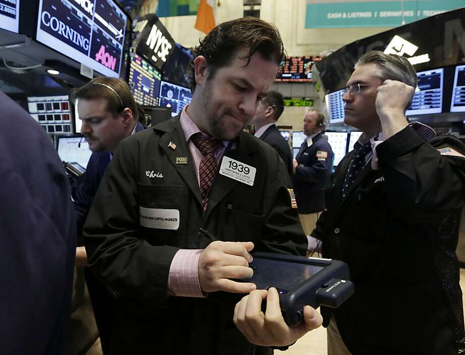 Trader Christopher Lotito (center) works on the floor of the New York Stock Exchange one day after Tuesday's phony tweet caused a temporary 1 percent drop in the Dow Jones industrial average. Photo: Richard Drew, Associated Press