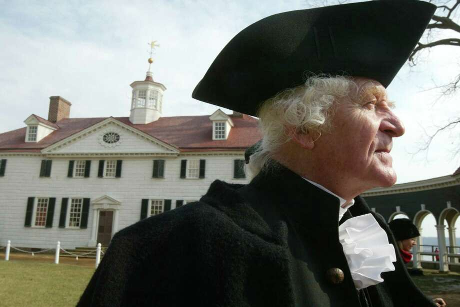 William Sommerfield, dressed as Gen. George Washington, waits to greet visitors outside a the first president's mansion at Mount Vernon, Va., on February 15, 2004. Photo: Alex Wong, Getty Images / 2004 Getty Images