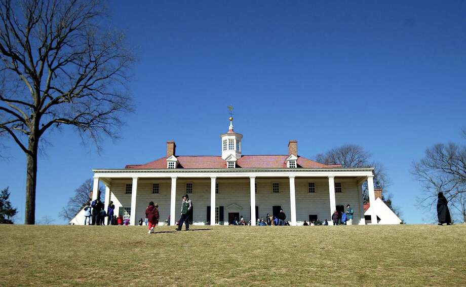 With George Washington's mansion in the background tourists make their way across a lawn on President's Day February 16, 2004 in Mount Vernon, Va. Photo: Brendan Smialowski, Getty Images / 2004 Getty Images