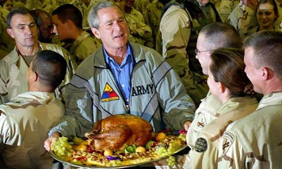 George W. Bush serves Thanksgiving dinner to troops in Baghdad. Getty Images. / 2003 AFP