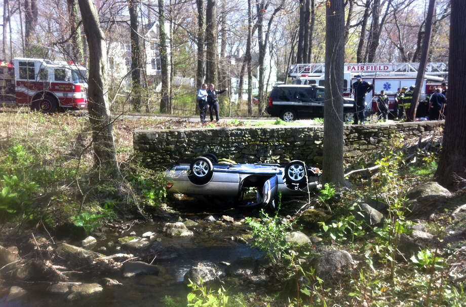Police and Fire personel respond to a car in creek at Osborne Hill Road and Glen Arden Drive in Fairfield, Conn. on Wednesday, April 24, 2013.Two brothers were hospitalized when their car flipped into a creek and started filling with water. Photo: Tim Loh / Connecticut Post