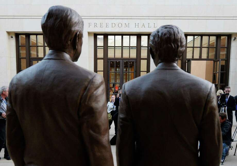 Bronze statues of former Presidents George W. Bush (R) and his father George H.W. Bush are on display during a tour of the George W. Bush Presidential Center on the campus of Southern Methodist University on April 24, 2013 in Dallas, Texas. Dedication of the George W. Bush Presidential Library is to take place on April 25 with all five living U.S. Presidents in attendance and an expected 8,000 people for the invitation-only dedication of the center . Photo: Kevork Djansezian, Getty Images / 2013 Getty Images