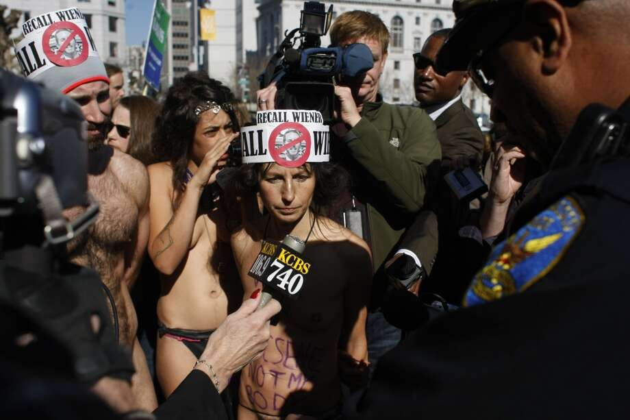 Gypsy Taub, center, and Trey Allen, left, come face to face with San Francisco Police after disrobing in front of city hall on Friday, Feb. 1. Protesters were demonstrating the city\'s ban on nudity which goes into effect today.