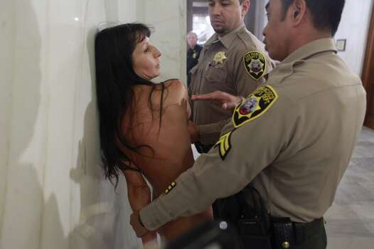 During a public hearing for legislation proposed by Supervisor Scott Wiener that would ban nudity on public streets, Gypsy Taub controlled by San Francisco County Sheriff\'s deputies outside the hearing after  taking her clothes off during the public comment session of the hearing in San Francisco City Hall on Monday Nov. 5, 2012 in San Francisco, Calif.