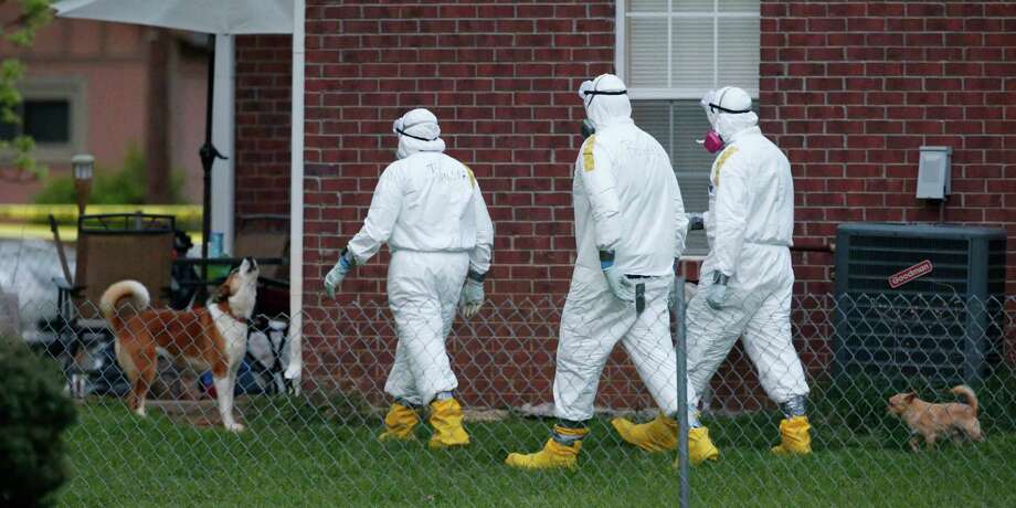 Federal agents wearing hazmat suits inspect the grounds around the house owned by Everett Dutschke, in connection with the recent ricin attacks, on Tuesday in Tupelo, Miss. No charges have been filed against him. Photo: Rogelio V. Solis, STF / AP