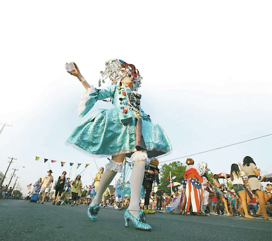 A member of King Anchovy's court takes part in the Fiesta Flambeau Parade in 2011. This year's parade features 150 participants. Photo: Express-News File Photo
