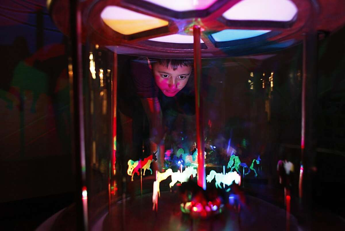 Zachary Perry, 8, looks into a merry-go-round at the Children's Discovery Museum in San Jose, Calif. on Saturday, April 20 2013. The Children's Discovery Museum opens its doors to children with autism for a one-night special.