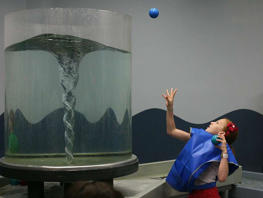 Katie Heathcote plays in the water area of the Children's Discovery Museum on a night for autistic children. Photo: James Tensuan, The Chronicle