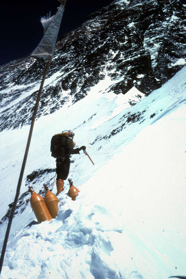 Prayer flags, Willi Unsoeld, oxygen bottles, and Mt. Everest. Photo: Tom Hornbein