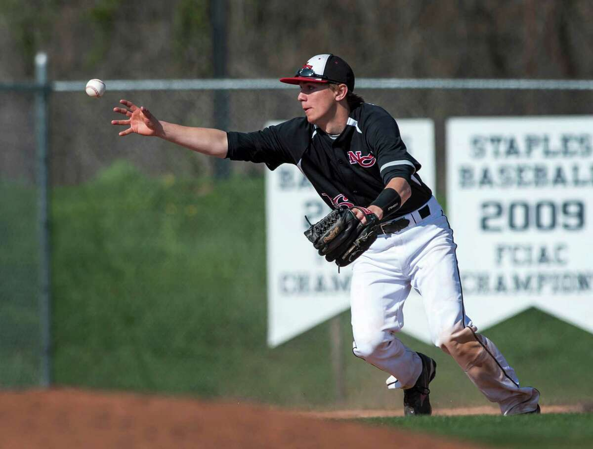 New Canaan high school third baseman Erik Jager can't get a handle on a ball in the infield during a baseball game against Staples high school played at Staples high school, Westport, CT on Wednesday April 24th, 2013.