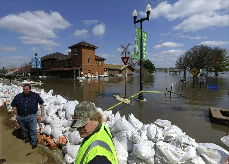 Peoria Maintenance Engineer Jim Clark (right) monitors a section of the sand bag wall holding back the Illinois River from recent flooding in Peoria, Ill. Photo: Seth Perlman / Associated Press