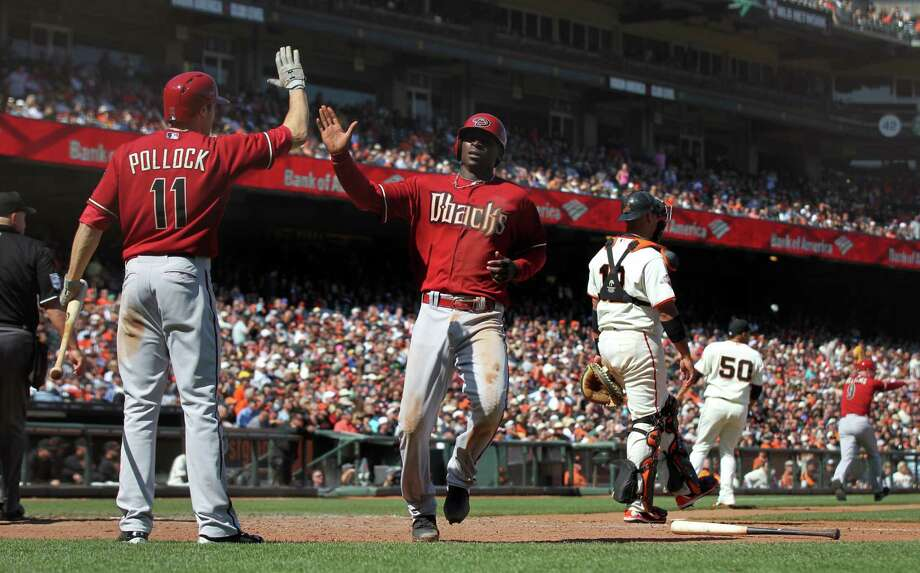 Arizona Diamondbacks Didi Gregorius #1 is greeted at home plate by A.J. Pollock #11 after scoring against the San Francisco Giants in the 9th inning of their MLB baseball game Wednesday, April 24, 2013 in San Francisco, California. Photo: Lance Iversen / The Chronicle / ONLINE_YES