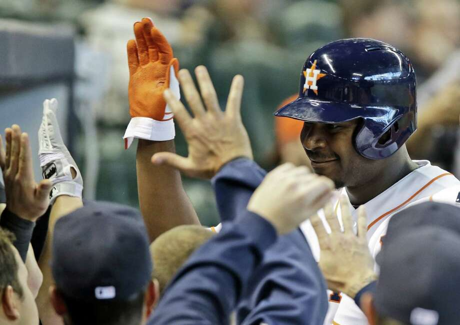 Houston's Chris Carter is greeted by his teammates in the dugout after hitting one of the Astros' three home runs Wednesday against Seattle. Photo: Pat Sullivan / Associated Press