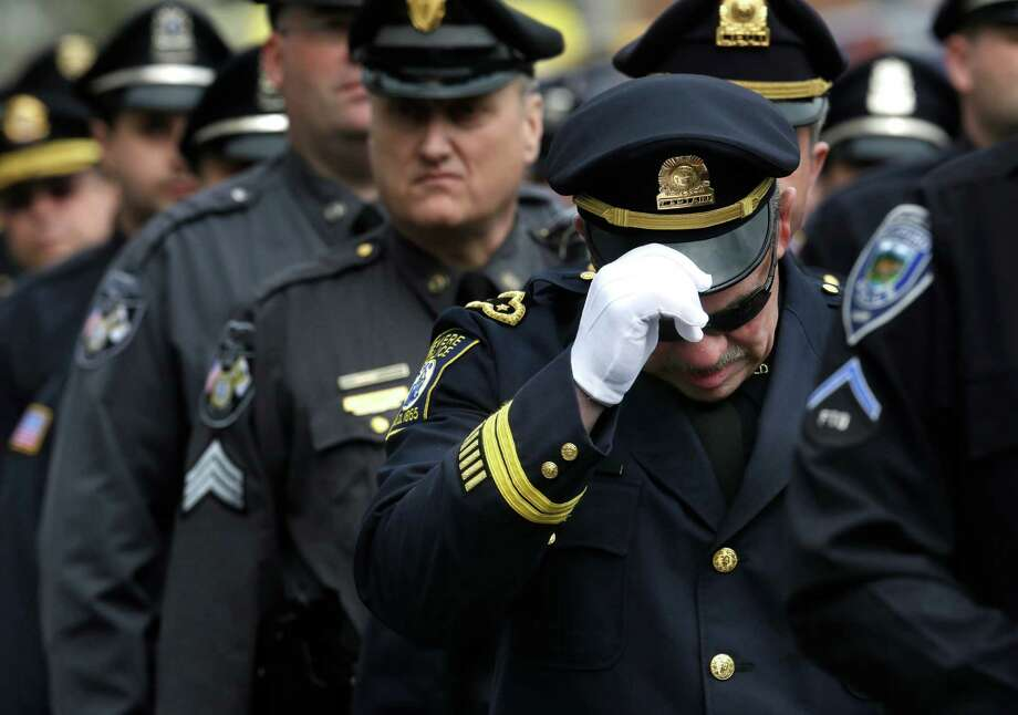A Revere, Mass. police captain holds his cap while entering a memorial service for fallen Massachusetts Institute of Technology police officer Sean Collier, in Cambridge, Mass., Wednesday, April 24, 2013. Collier was fatally shot on the MIT campus Thursday, April 18, 2013. Authorities allege that the Boston Marathon bombing suspects were responsible. (AP Photo/Steven Senne) Photo: Steven Senne