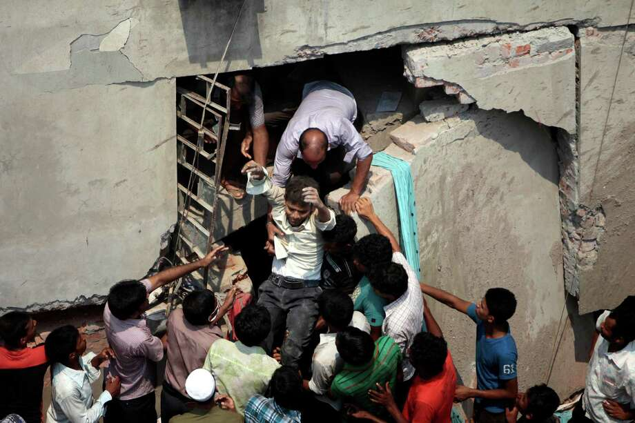 A man who was trapped in an collapsed eight-story building housing several garment factories is reccued in Savar, near Dhaka, Bangladesh, Wednesday, April 24, 2013. Dozens were killed and many more are feared trapped in the rubble. (AP Photo/ A.M. Ahad) Photo: A.M. Ahad