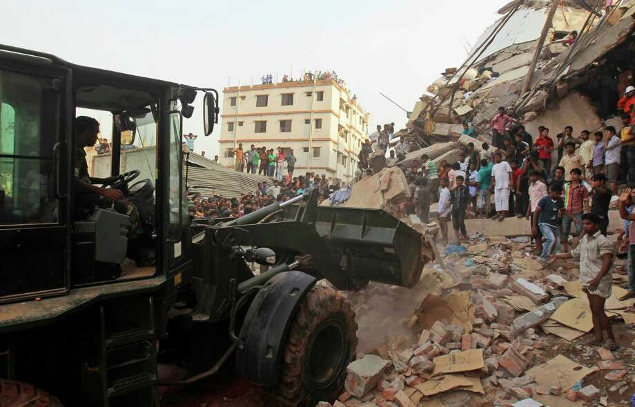 Bangladeshi soldiers use an earthmover during a rescue operation at the site of a building that collapsed  a building collapse in Savar, near Dhaka, Bangladesh, Wednesday, April 24, 2013. An eight-story building housing several garment factories collapsed near Bangladesh's capital on Wednesday, killing dozens of people and trapping many more under a jumbled mess of concrete. Rescuers tried to cut through the debris with earthmovers, drilling machines and their bare hands. (AP Photo/A.M.Ahad) Photo: A.M. Ahad