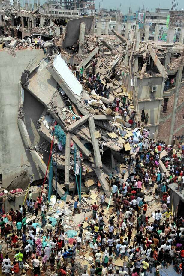 People and rescuers gather after an eight-story building housing several garment factories collapsed in Savar, near Dhaka, Bangladesh, Wednesday, April 24, 2013. Dozens were killed and many more are feared trapped in the rubble. (AP Photo/ A.M. Ahad) Photo: A.M. Ahad