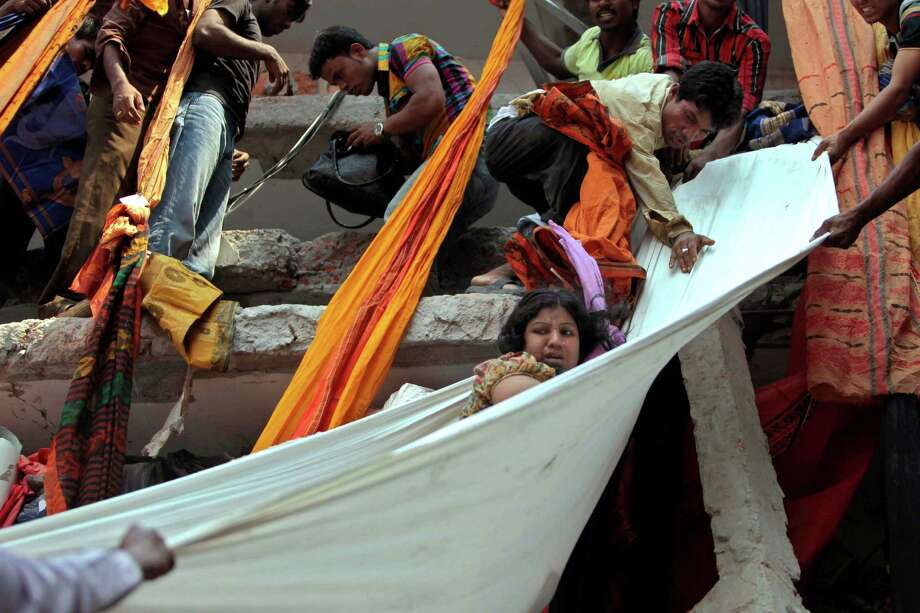 Rescue workers use pieces of clothes to bring down a survivor after an eight-story building housing several garment factories collapsed in Savar, near Dhaka, Bangladesh, Wednesday, April 24, 2013. Dozens were killed and many more are feared trapped in the rubble. (AP Photo/ A.M. Ahad) Photo: A.M. Ahad