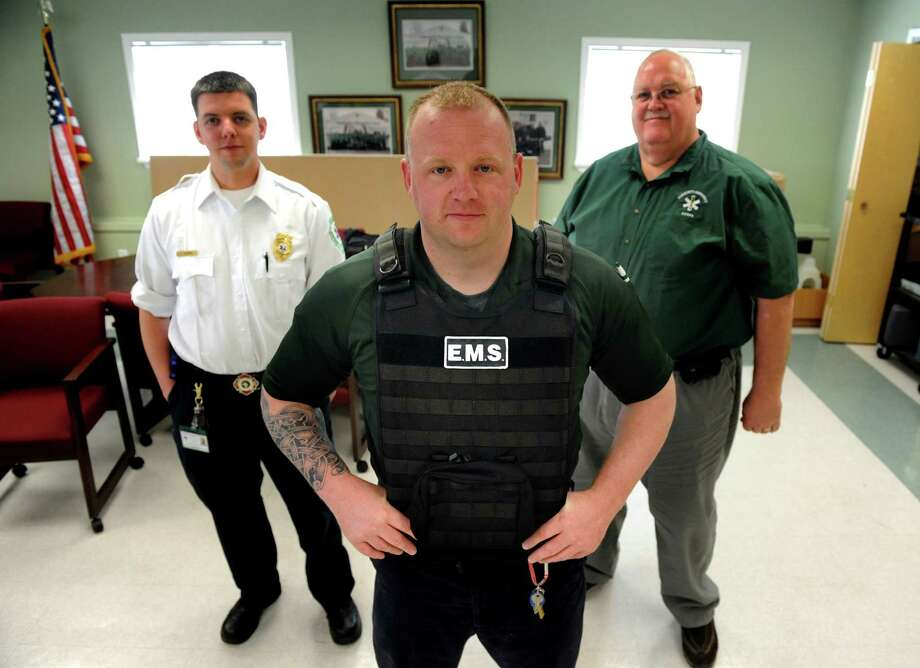 Paramedic Brian Heaney, center, wears body armor as he stands with assistant chief Timothy Thomas, left, and executive director Ray Otten on Wednesday, April 24, 2013, at Community Emergency Corps. in Ballston Spa, N.Y. (Cindy Schultz / Times Union) Photo: Cindy Schultz / 10022107A