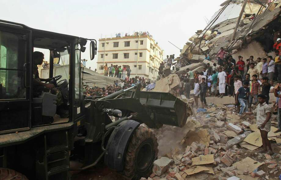 Soldiers use an earthmover at the site of a building collapse in Savar, near Dhaka, Bangladesh. Garment factories ordered employees to work despite safety risks discovered the day before. Photo: Photos By A.M. Ahad / Associated Press