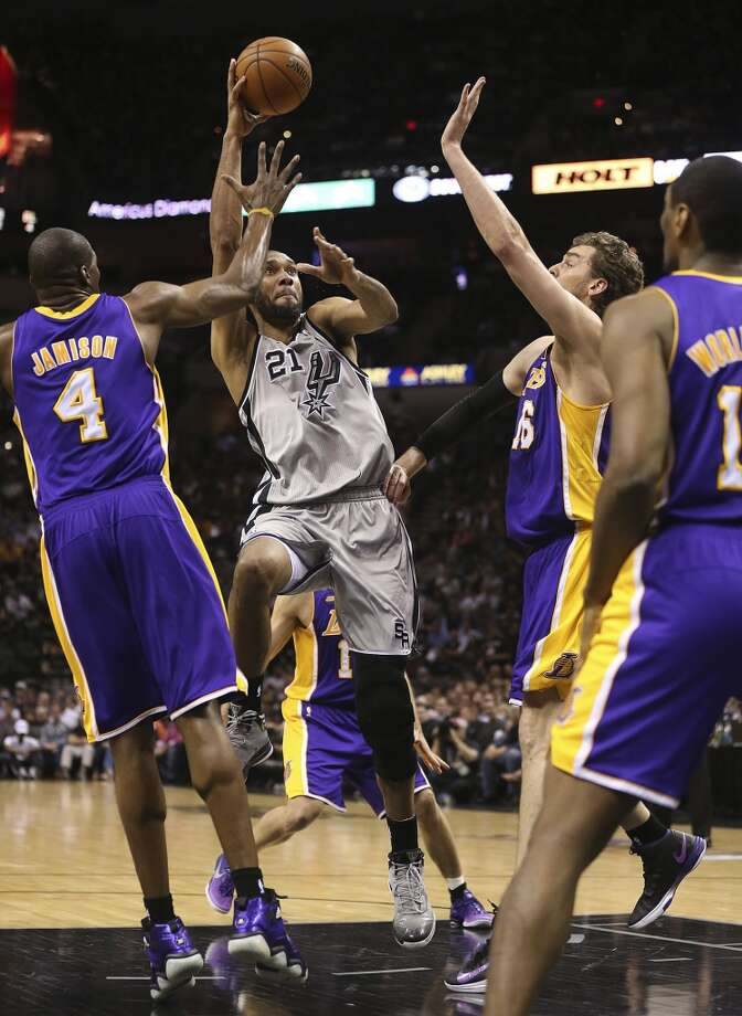 San Antonio Spurs' Tim Duncan shoots between Los Angeles Lakers' Antawn Jamison, (4), Pau Gasol and Metta World Peace in the first half of game 2 in the first round of the NBA Playoff at the AT&T Center, Wednesday, April 24, 2013.