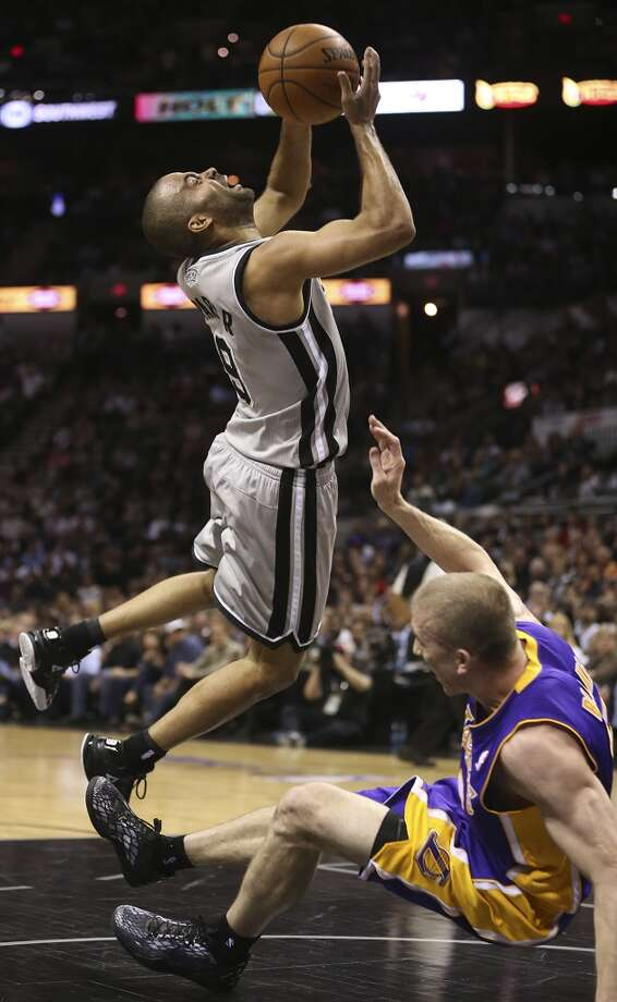 San Antonio Spurs' Tony Parker runs into Los Angeles Lakers' Steve Blake as he drives to the basket in the first half of game 2 in the first round of the NBA Playoff at the AT&T Center, Wednesday, April 24, 2013.