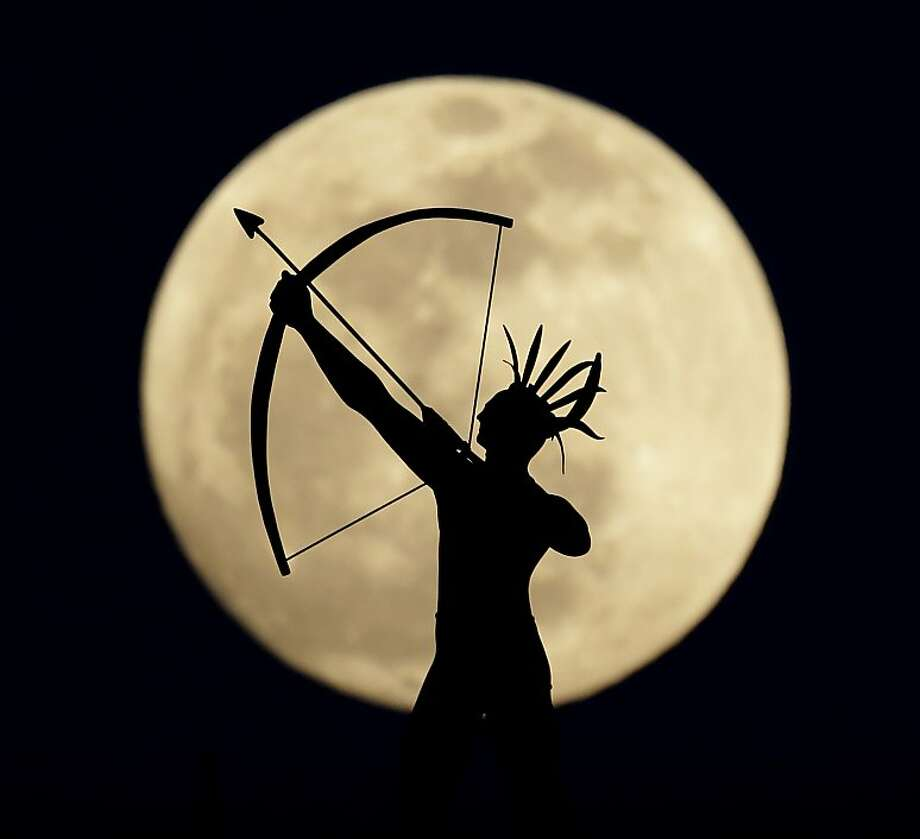 A full moon rises behind a statue of a Kansas Indian on top of the Kansas Statehouse Wednesday, April 24, 2013, in Topeka, Kan.  Photo: Charlie Riedel, Associated Press