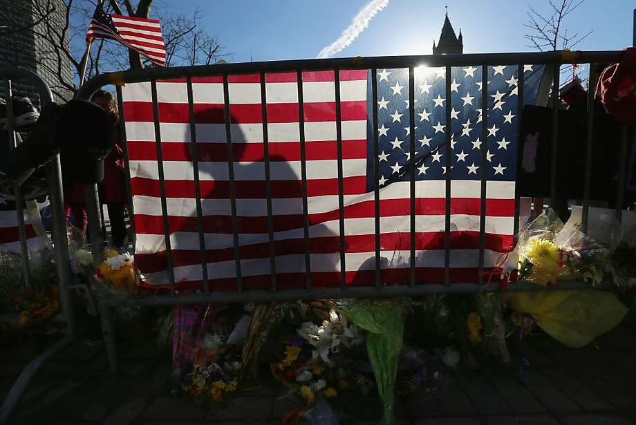 A person's shadow is cast on an American flag at a makeshift memorial in Copley Square, near the site of one of the Boston Marathon bombings, on April 24, 2013 in Boston, Massachusetts. Boylston Street, the site of both bombings, finally fully reopened to the public today along with Copley Square.  Photo: Mario Tama, Getty Images