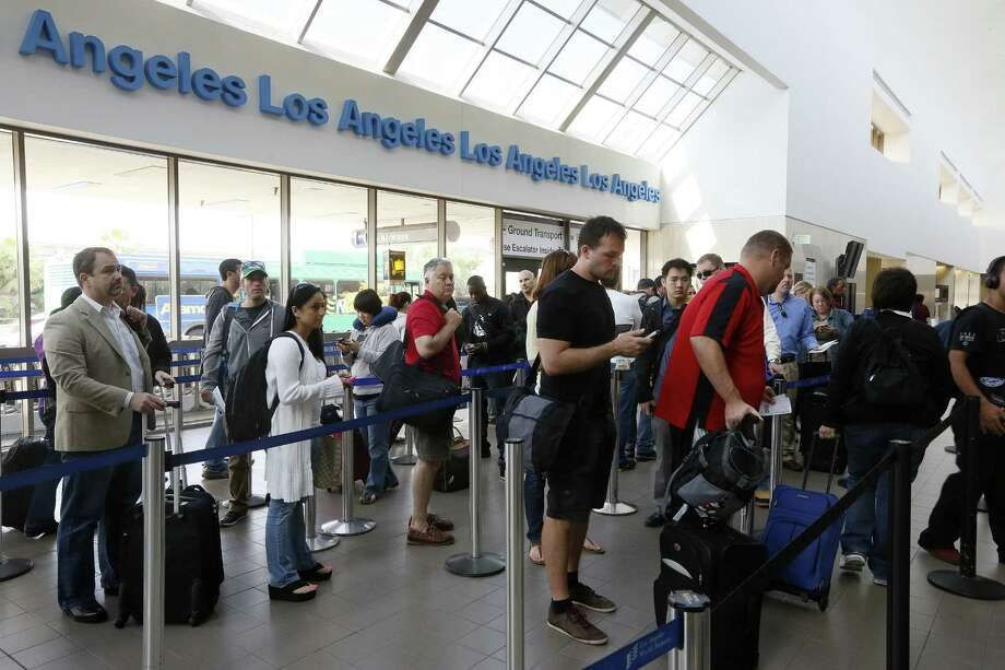 Lines like this at Los Angeles International Airport are becoming familiar, and the FAA administrator cites automatic budget cuts as exacerbating delays. Photo: Damian Dovarganes / Associated Press