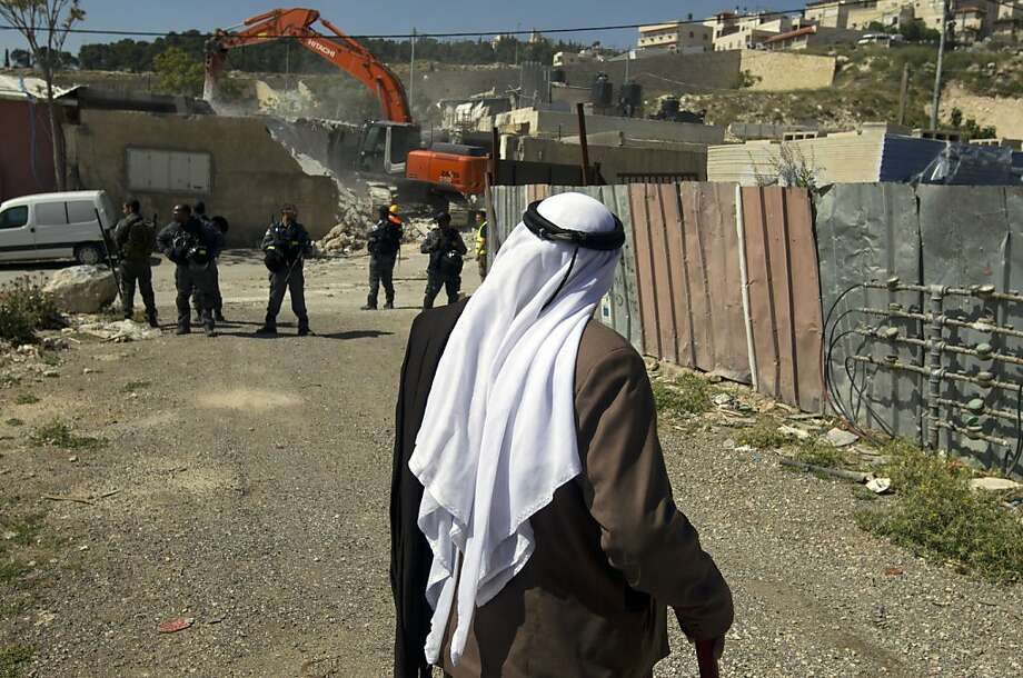 A Palestinian man looks on as his house is demolished by a bulldozer hired by the Jerusalem municipality in the Israeli annexed East Jerusalem neighborhood of al-Tur on April 24, 2013. Palestinian homes built without a construction permit are often demolished by order of the Jerusalem municipality.  Photo: Ahmad Gharabli, AFP/Getty Images