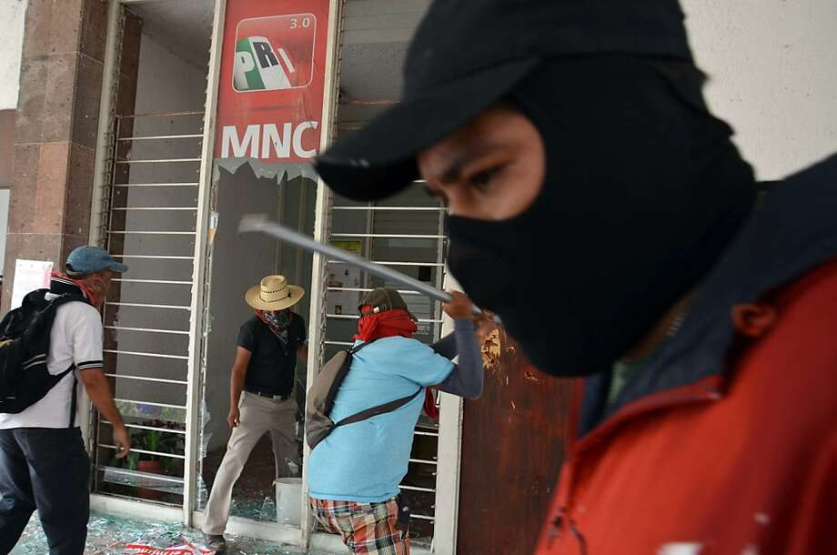 Protesting against President Pena Nieto's education reform project, teachers break out windows during an attack on the Revolutionary Institutional Party, PRI, regional offices, causing significant damage, in Chilpancingo, Mexico, Wednesday April 24, 2013. Thousands of elementary and high-school teachers in Guerrero, one of the country's poorest and worst-educated states, walked off their jobs more than a month ago, turning away hundreds of thousands of children from their classrooms and since launched an increasingly disruptive string of protests.  Photo: Alejandrino Gonzalez, Associated Press
