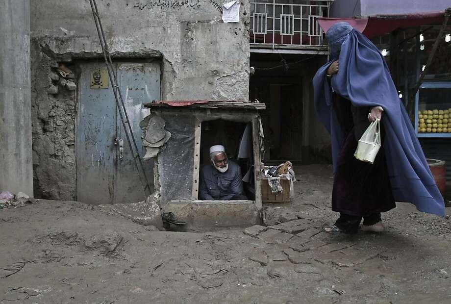 An Afghan woman walks past a street vendor as he waits for customers on the outskirts of Kabul, Afghanistan, Wednesday, April 24, 2013.  Photo: Rahmat Gul, Associated Press
