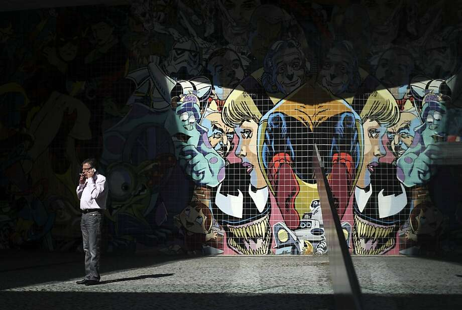 A man talks on a cell phone next to a tiled wall decorated with comic characters, reflected in a glass on the right, in a business district in Lisbon, Wednesday, April 24, 2013.  Photo: Francisco Seco, Associated Press